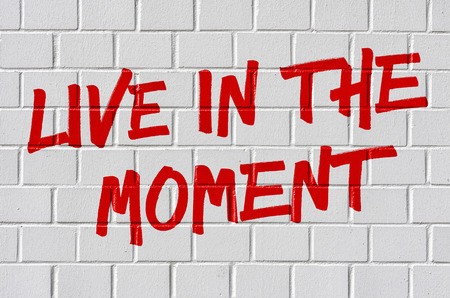 54780441 - graffiti on a brick wall - live in the moment